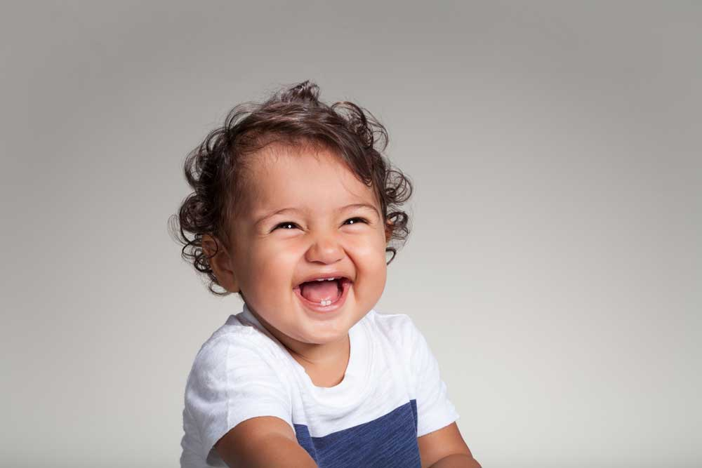 Baby with curly hair laughing