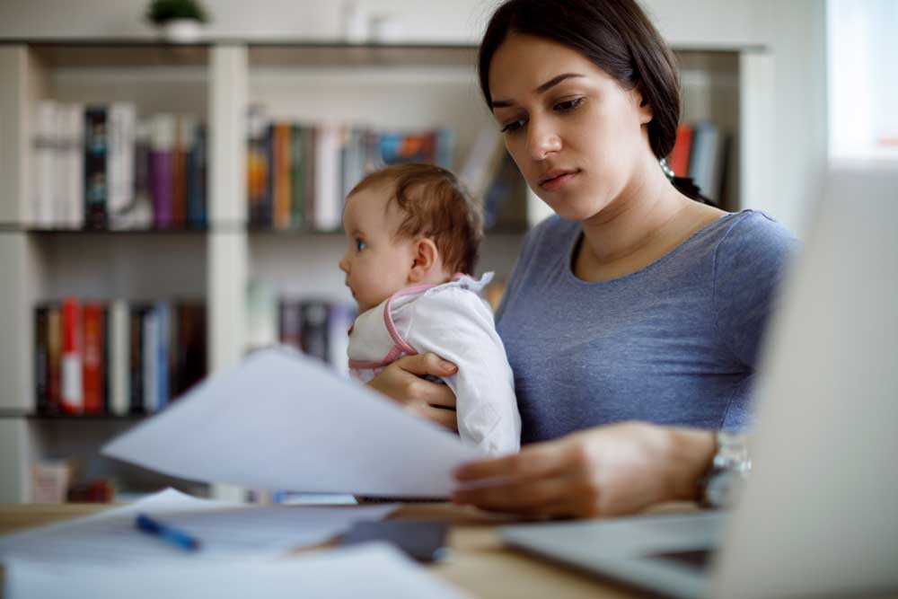 Young worried mother working from home