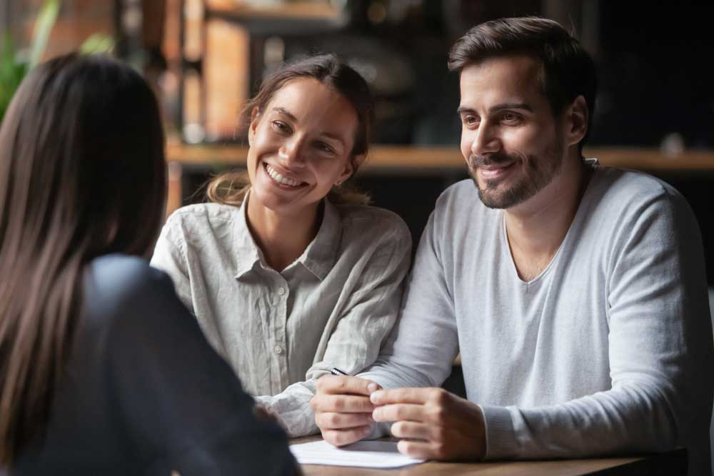 Diverse couple communicating with real estate agent, successful meeting ready to sign contract concept