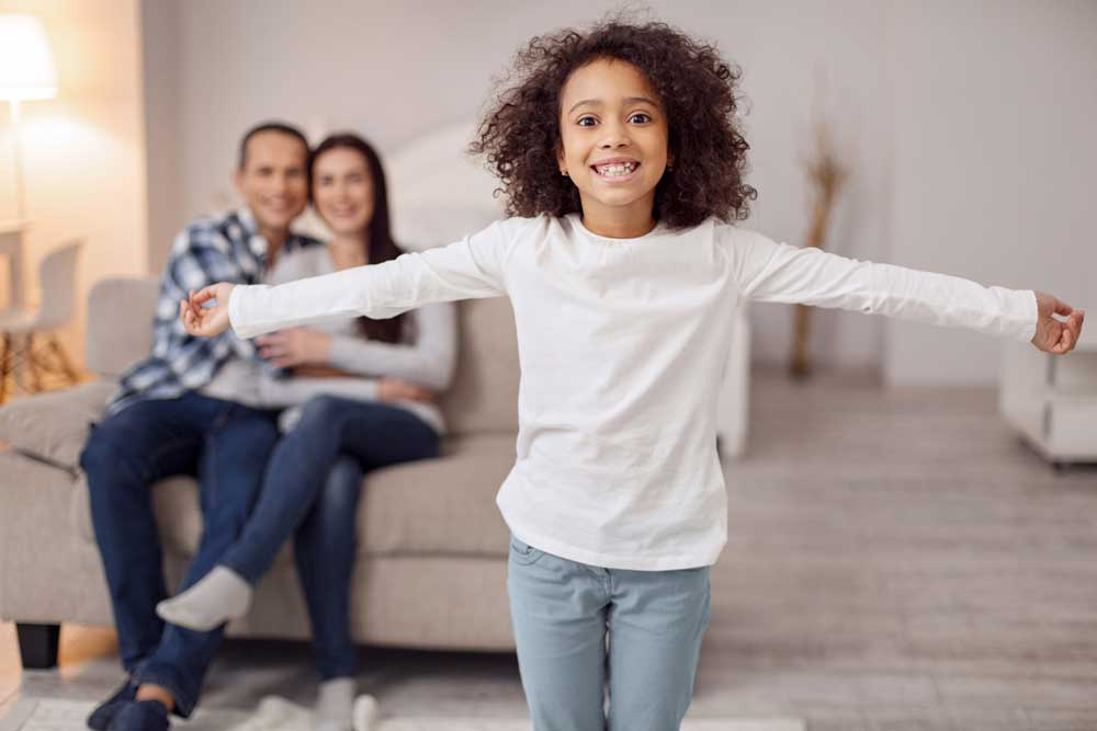 Pretty cheerful curly-haired girl smiling and spreading her arms and her parents sitting on the couch in the background