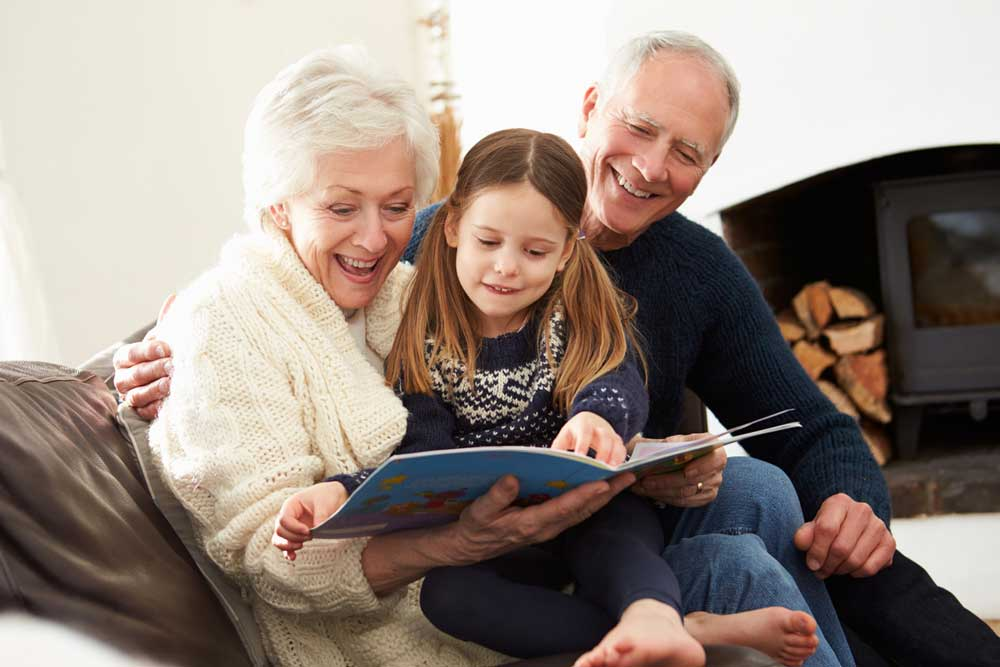 Grandparents And Granddaughter Reading Book At Home Together Relaxing
